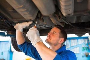 Mechaniker untersucht unter dem Auto