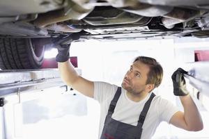 männlicher Reparaturarbeiter, der Auto in Werkstatt untersucht foto