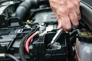 Hand eine Klammer in einem Automotor festziehen foto
