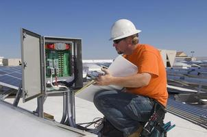 Elektrotechniker, der Buch hält, während Elektrizitätskasten analysiert foto
