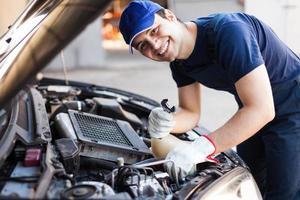 Mechaniker, der einen Automotor repariert foto
