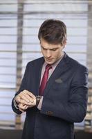 beschäftigter Mann im Anzug, der auf seine Uhr schaut foto