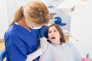 Kinderzahnarzt untersucht ihre junge Patientin foto