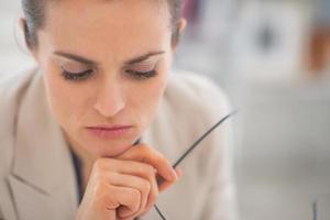 Porträt der nachdenklichen Geschäftsfrau mit Brille im Büro foto