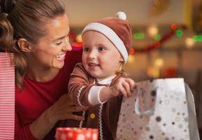 glückliche Mutter und Baby, die Weihnachtseinkaufstaschen überprüfen
