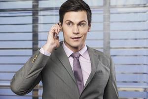 selbstbewusster, lächelnder Geschäftsmann am Telefon foto