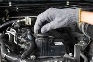 Der Mechaniker öffnet den Öldeckel eines Automotors. foto