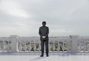 Geschäftsmann, der auf Balkon steht foto