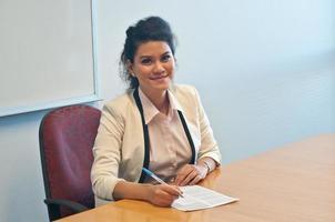 Geschäftsfrau, die Vertragsvereinbarung im Amt unterzeichnet foto
