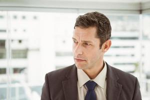 nachdenklicher Geschäftsmann, der Büro wegschaut foto