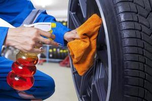 Techniker, der einen Reifen in der Werkstatt reinigt foto