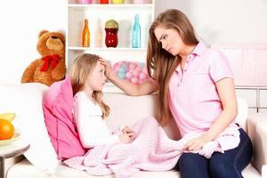 besorgte Mutter und krankes Kind zu Hause foto