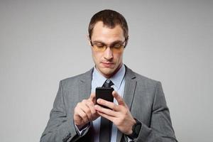 junger Geschäftsmann, der ein Mobiltelefon benutzt foto