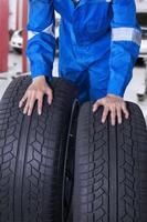 zwei Reifen mit Mechaniker in Werkstatt foto