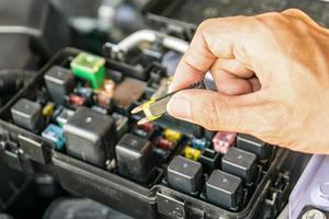 Automechaniker, der eine Autosicherung überprüft foto