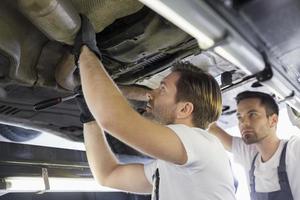 männliche Reparaturarbeiter, die Auto in Werkstatt untersuchen foto