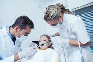 männlicher Zahnarzt mit Assistent, der Mädchenzähne untersucht foto