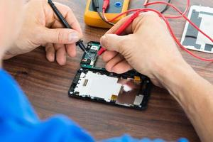 Techniker repariert Handy mit Multimeter