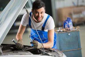 lächelnder Mechaniker, der am Motor arbeitet foto