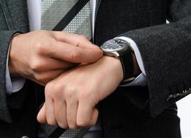 Geschäftsmann stellt die Zeit auf seiner Armbanduhr ein foto