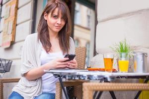 schöne Frau hält Handy.