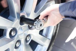 Mechaniker wechselt das Rad am Auto foto
