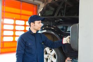 Mechaniker, der das Autorad in der Autowerkstatt wechselt foto