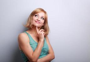 schöne denkende glückliche lässige Frau, die mit natürlichem em aufblickt foto