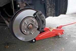 ein Bremsrotor an einem aufgebockten Auto foto