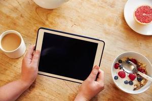 Person, die digitale Tablette beim Frühstück betrachtet foto