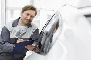 Selbstbewusster Automechaniker, der die Zwischenablage hält, während er sich an das Autofenster lehnt foto