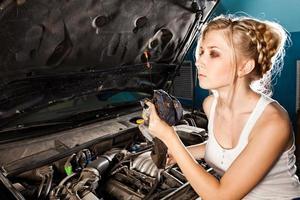 Mädchen überprüft den Ölstand im Auto foto