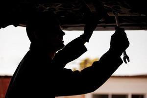 junger Mechaniker, der ein Auto repariert foto