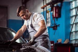 uniformierter Mechaniker in der Tankstelle foto