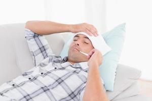 Mann misst die Temperatur auf dem Sofa foto