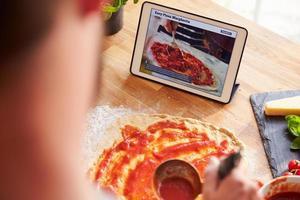 Person, die Pizzarezept mit App auf digitalem Tablet folgt foto