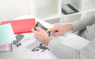 Geschäftsmanns Hände mit Taschenrechner foto
