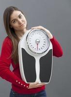 schlankes 20s Mädchen, das ein Fitness- und Gewichtskontrollsymbol hält