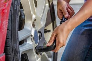 Frau wechselt Reifen mit Radschlüssel foto