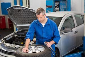 fokussierter Mechaniker, der den Reifen aufpumpt foto