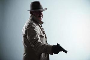 Silhouette des Detektivs mit Schnurrbart und Hut. Pistole halten.