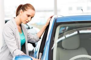 Frau, die Auto betrachtet foto