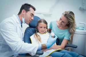 Zahnarzt lehrt Mädchen, wie man Zähne putzt foto