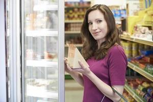 Frau, die Sandwich vom Supermarkt kauft foto