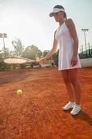 attraktive Tennisspielerin, die einen Ball schlägt foto