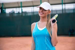 Porträt einer glücklichen Sportfrau, die Tennis spielt foto