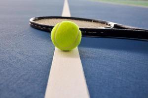 Tennisball und Schläger auf dem Platz foto