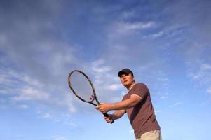 junger Tennisspieler wartet Ball im Netz