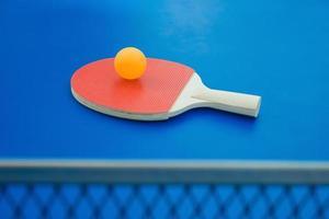 Tischtennisschläger und Ball und Netz auf Tischtennisplatte foto