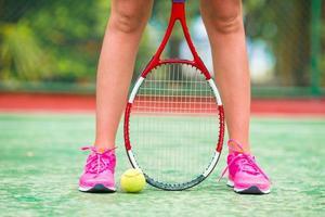Schuhe mit Tennisschläger und Ball auf dem Platz foto